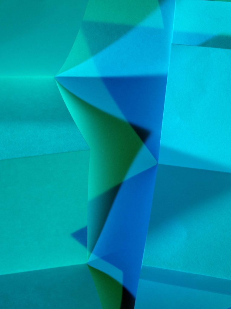 A color photograph of paper airplanes lit with blue and green lights.