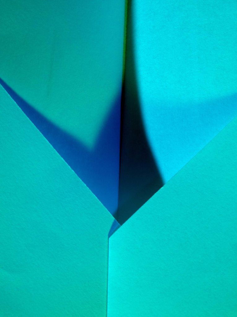 A close up photograph of a paper airplane lit with blue and green light.