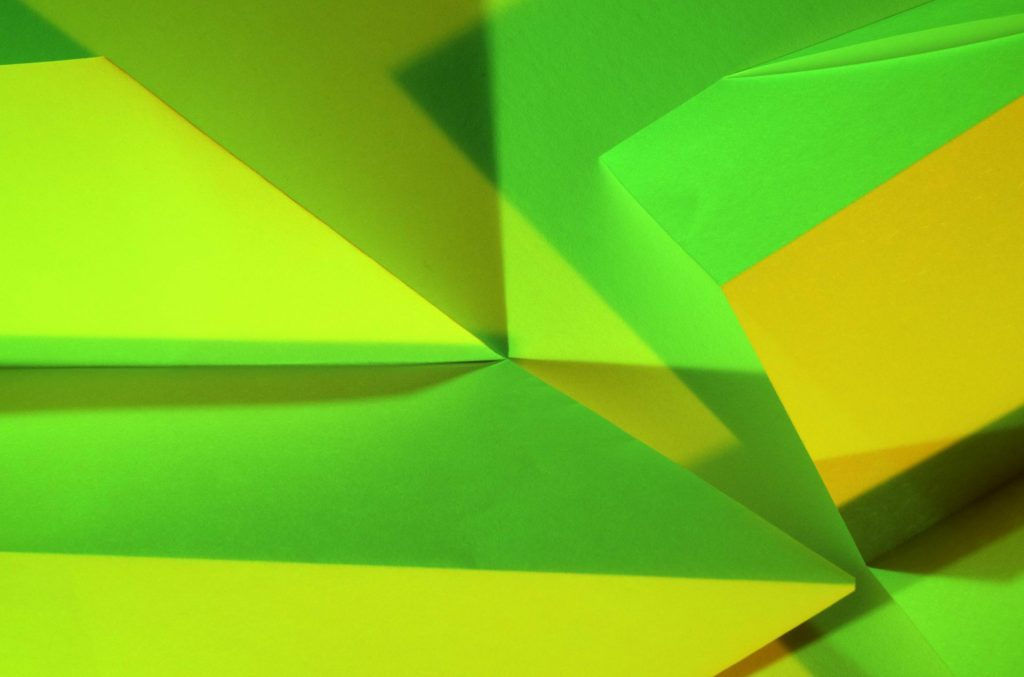 Paper planes lit with green and yellow light